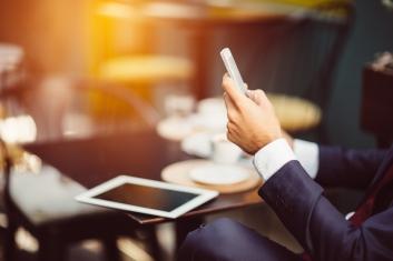 Businessman texting at sidewalk cafe